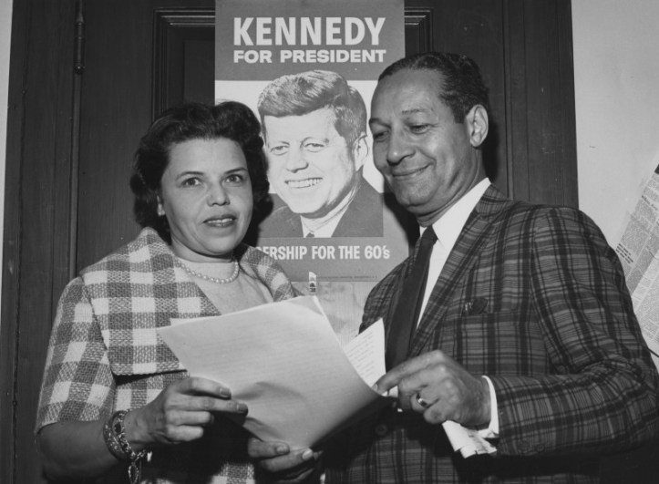"""PC1771 ca. 1960 Marjorie Lawson (left) stands with an unidentified man infront of a poster for John F. Kennedy's 1960 Presidential Campaign Please credit: """"Copyright Maurice Sorrell. President's Collection Photographs. John F. Kennedy Presidential Library and Museum, Boston"""""""