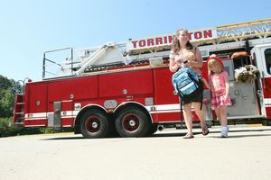 East Elementary School kindergartner Eliana Knapp, 5, walks with her mother, Lisa, to the school's front door after riding to Eliana's first day of school aboard the Torrington Fire Department's ladder truck. Knapp won the honor in a drawing co-sponsored by the school district and the Torrington Early Childhood Collaborative. Jim Moore Republican-American.