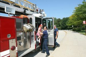East Elementary School kindergartner Eliana Knapp, 5, gets a lift from firefighter Mark Garrison after riding to her first day of school on board the city's ladder truck Tuesday. Knapp won the honor in a drawing co-sponsored by the school district and the Torrington Early Childhood Collaborative. Jim Moore Republican-American.