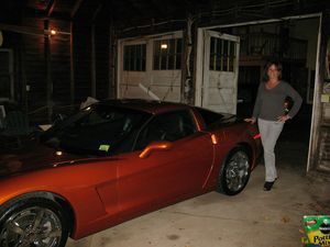 Debra Testa poses with her 2009 Corvette she won in the City Hall Veterans Memorial Wall raffle, which raised $85,000. Testa won the car after buying a single ticket, and Mayor Ryan J. Bingham and Royals Garage owner Glenn Royals delivered the car to Testa's home on Tuesday. Kevin Litten / Republican-American