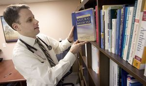 Dr. Shawn Carney of Northeast Natural Medicine refers to a book he uses for reference in his office in Newtown Wednesday. Steven Valenti Republican-American