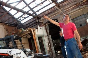 Carl Begley , owner of C&D Services in Wolcott, points to trusses inside the old Matthews & Willard Manufacturing Co. on Cherry Avenue in Waterbury on Wednesday. The trusses will be recycled for use in a barn and a cabin in the White Mountains in New Hampshire. Darlene Douty Republican-American
