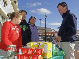 State Sen. Andrew Roraback purchases a box of cookies while talking about the importance of voting to Girl Scout Kassidy Campbell with her mother Ingrid Campbell and Linda Paiva all from troop 66810 in Canton as he campaigns along The Shoppes at Farmington Valley in Canton Saturday afternoon. Michael Kabelka / Republican-American