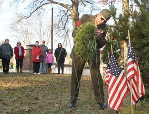 US Army Pastor McGee presents a wreath at the soldier´s memorial at Forest View Cemetery during a Wreaths Across America ceremony in Winsted on Saturday afternoon. Specially designed wreaths for the Army, Marines, Navy, Air Force, Coast Guard, Merchant Marine and POW/MIA were placed in front of the DAR Memorial Stone and flag pole to remember all soldiers, sailors, airmen, and marines who served, honor their sacrifices, and teach the younger generations about the high cost of our freedoms. An honor guard, rifle salute, and Taps were provided by VFW Post No. 296. The Wreaths Across America story began over 20 years ago when the Worcester Wreath Company from Harrington, Maine, initiated a tradition of donating and placing wreaths on the headstones of our Nation's fallen heroes at Arlington National Cemetery. In 2012 it is projected that more than 400,000 wreaths will be placed nationwide. Michael Kabelka Republican American
