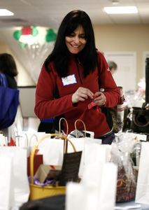 Toni Ambrose of White Plains, N.Y., places raffle tickets in various items at a silent auction during a fundraiser Sunday at the Middlebury Racquet Club in Middlebury. The event featured a raffle, therapy dogs, members of various local tennis teams and an assortment of tennis activities to raise money for Sandy Hook School Support Fund. Christopher Massa/RA