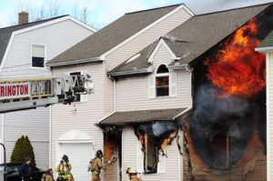Fire burns through a house at 64 Griswold St. in Torrington on Monday. Alec Johnson/RA