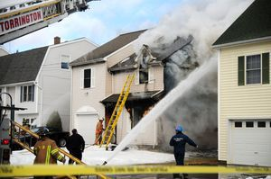Firefighters work to control a fire at 64 Griswold St. in Torrington on Monday. Alec Johnson/RA