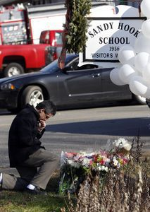 A man pays his respects at a memorial outside Sandy Hook Elementary School in Newtown in December. The federal government will be asked to pay some of the construction costs of a new Sandy Hook Elementary School, the site of a mass murder Dec. 14 when 20 first-graders and six adults were killed by a gunman. Republican-American archive