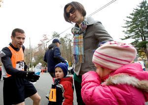 Kyle Morse of Waterbury is greeted at the finish line by his wife, Sue Morse and his children Thomas, 3, and Eva, 5, after finishing first in the sixth annual Pilgrim's Pace 5K, sponsored by the Middlebury Congregational Church, in Middlebury Saturday. Thomas and Eva competed in the children´s fun run around the green.  Steven Valenti Republican-American