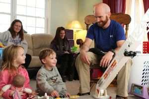 David Lafferty, right, plays with his niece and nephew, Matthew and Makayla Gill, both 4, shortly after returning to his Watertown home Monday. Lafferty spent the past six months in Afghanistan as a private contractor for the U.S. military. In the background, Lafferty's sister, Jenn Lafferty, left, and fiance, Meghan Walker, look on. Laraine Weschler/RA