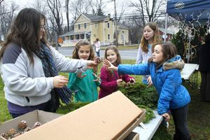 BETHLEHEM, CT- 08 DECEMBER 2012 120812JW02 - Michelle Wall hands out pine cone decorations to Olivia Kennedy age 9, Claire Wall age 9 Kara Cheetham age 12 and Emma Gagnon age 10 to decorate wreaths with during the Bethlehem 32nd Annual Christmas Town Festival Saturday morning. The proceeds of the sales go to benefit the Bethlehem Christian Fellowship Youth Program.   Jonathan Wilcox Republican American.