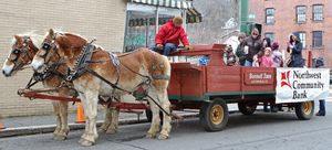 Rick Bunnell from Bunnell Farm in Litchfield looks back as revelers board his wagon during Main Street Christmas festivities in Winsted. Michael Kabelka/Republican-American