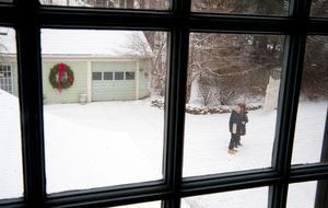 A couple stand outside the McCarthy home in the snow. Money raised from the house tour will benefit local charities.