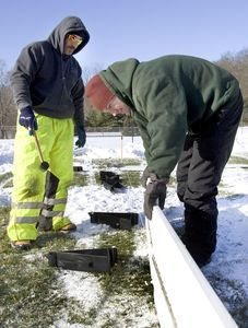 Tom Farrelly and Dave Carbonaro, both of Southbury Public Works, help to put up the town's portable ice skating rink at Community Park on Monday. Steven Valenti/RA