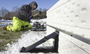 Tom Farrelly of Southbury Public Works helps to put up the town's portable ice skating rink at Community Park on Monday. Steven Valenti/RA