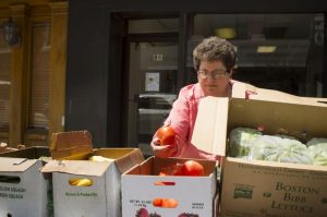 Sue Pronovost puts fresh vegetables in boxes outside of the Brass City Harvest headquarters along Bank Street in downtown Waterbury Thursday. Erin Covey Republican-American.