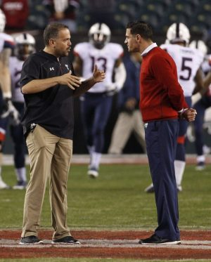 Temple head coach Matt Rhule, left, talks with Connecticut head coach Bob Diaco, right, during warm-ups prior to the first half of an NCAA college football game, Saturday, Nov. 28, 2015, in Philadelphia. (AP Photo/Chris Szagola)