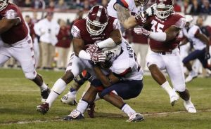 Temple linebacker Avery Williams, left, takes down Connecticut running back Arkeel Newsome, right as he runs with the ball during the first half of an NCAA college football game, Saturday, Nov. 28, 2015, in Philadelphia. (AP Photo/Chris Szagola)