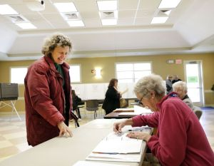 Christopher Massa Republican-American Woodbury resident Pam Hurt, left, checks in with Pat Gage at Woodbury Senior Center on Tuesday. Residents came out to vote on the proposed Aquarion Reservoir purchase.