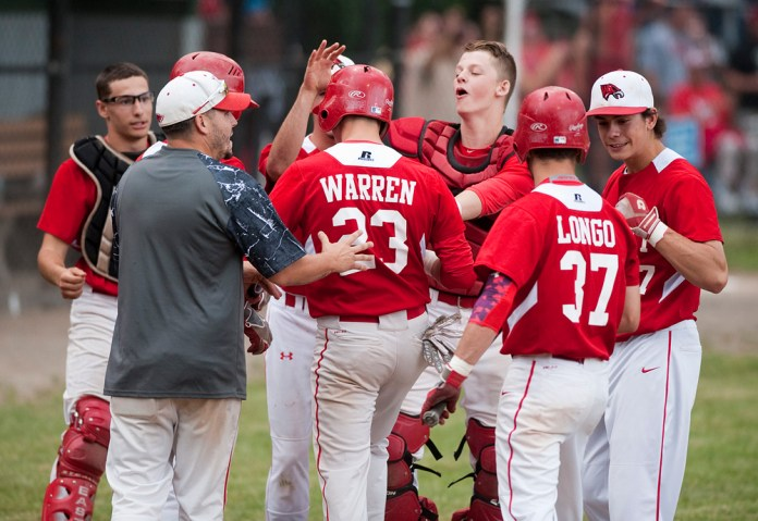 Wolcott's Matthew Warren (23) and Nicolas Longo (37) are congratulated by teammates after coming in to score on a double by Jacob Gabriel during their Class M semi-final game against Haddam-Killingworth Tuesday at Sage Park in Berlin. Jim Shannon Republican-American