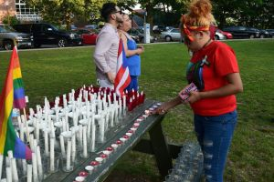 Jazzlin Rodriguez, 20, of Waterbury, lights candles in rememberance of the Orlando shooting victims while volunteering at a vigil held at Library Park Thursday night. Jacqueline Stoughton Republican-American