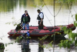 Thomaston Dive Team members Richard Galpin, left, and Marc DiBennedetto, in the boat, talk with diver Kevin Robinson during the search for a weapon in a small pond off Pearl Lake Road in Waterbury in 2006. Republican-American Archive