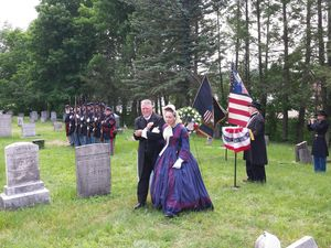 Rebecca Runk is escorted back to her seat during a dedication ceremony for a headstone on what is believed to be the grave site of Pryce Lewis. Runk's late husband, Wilber