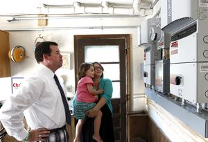 Kenny and Katie Curran of Waterbury, talk about the control area which feeds in from the solar panels, at their home in Waterbury on Friday. Also in the photo is their daughter, Annie, 3. The Currans had solar panels installed on their home less than a year ago. Christopher Massa Republican-American