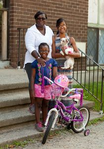 WATERBURY, CT-18 August 2014-081814BF03- LaTeena Bartee, 26, right, poses for a portrait with her dog Daisy, her mother Angela Holmes and her younger sister Mickal Holmes, 8. Bartee started a program called Young Civic Learners in 2011 which instructs kids on the law, civics and citizenship. It is a volunteer program to initiate middle school students into the workings of government. Bob Falcetti Republican-American