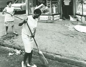 Women clean broken glass from the street after a disturbance in North Square in 1967. Republican-American archive