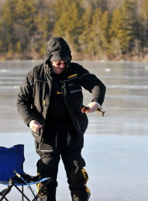 Phil Kozlak of Torrington examines a pickerel he caught while ice fishing Friday on Burr Pond in Torrington. Alec Johnson/ Republican-American