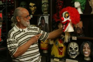 Michael Rinaldi, owner of Arabesque Dance and Costume on Bank Street in Waterbury, plays with a scary clown mask at his store Wednesday. Laraine Weschler Republican-American