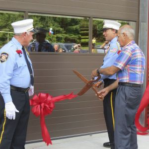 cutline attribution name:Ruth Epstein Republican-American Former fire chiefs David Seney, left, and Curt Mechare, right foreground, help current chief Tim Downs cut the ribbon on the new Emergency Services Center in Falls Village during a ceremony Sunday.