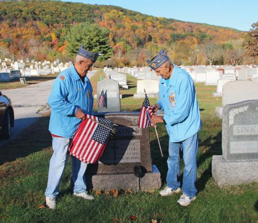 cutline attribution name:Luke Marshall Republican-American Brothers Manny Matos, left, and Bill Matos, both U.S. Air Force veterans, place flags on the graves of veterans at St. James Cemetery in Naugatuck on Oct. 27 in preparation for Veterans Day.
