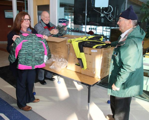 Lisa Heuschkel, school social worker at Litchfield High School, holds one of 24 winter jackets delivered to the high school Thursday by Art Coffill, center, and Evan Williams, members of the St. Anthony's Council of the Knights of Columbus of Litchfield. The jackets donated by the council will be distributed to needy students in the town's school system. John McKenna Republican-American