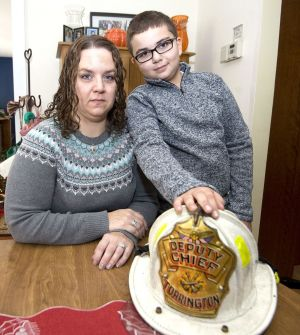 Lori Pepler, wife of late Torrington Deputy Fire Chief Christopher Pepler, and their son, Nathan, 10, pose with Christopher's fire helmet at their Torrington home on Thursday. Jim Shannon Republican-American