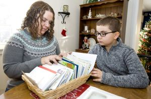 Lori Pepler, wife of late Torrington Deputy Fire Chief Christopher Pepler, and their son, Nathan, 10, look through a basket of condolence letters at their Torrington home on Thursday. Jim Shannon Republican-American