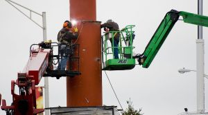 WATERBURY, CT-111117JS06-Workers from Custom Finishers, Inc. of Levittown, Penn., weld support columns for a new sign being installed in front of the Brass Mill Center in Waterbury on Tuesday.   Jim Shannon Republican-American
