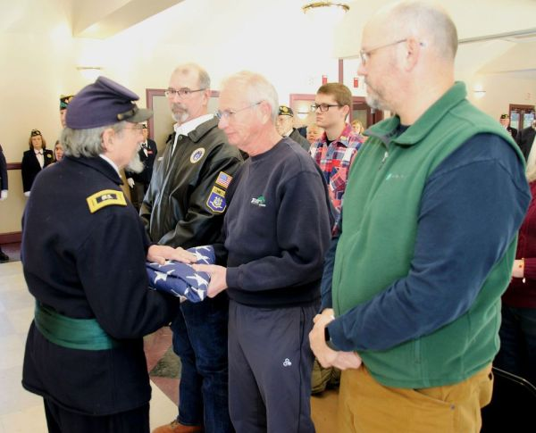Allyn Sedgwick of Torrington, a descendant of American Legion Post 44 of Bantam's veteran of the month, Civil War Maj. Gen. John Sedgwick, presents a flag to Dane Deleppo of the 2nd Connecticut Heavy Artillery re-enactment group Saturday at the Bantam Borough Hall. With Sedgwick are his brother, Thomas Sedgwick, left, of New Hartford, and their nephew, William Sedgwick of Harwinton. John McKenna Republican-American
