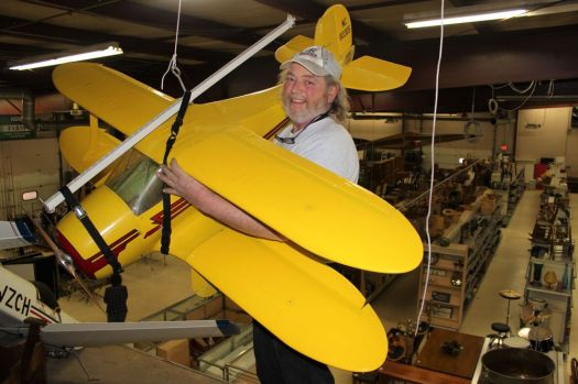 Merton Larmore III came up with a pulley system to easily hang 16 wood airplanes from the ceiling of his new store, Litchfield County Pickers South in New Milford. Alicia Sakal/ Republican-American
