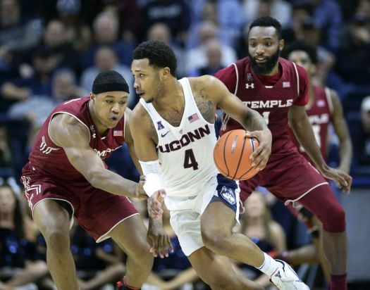 Connecticut's Jalen Adams (4) controls the ball against Temple's J.P. Moorman II (4) and Josh Brown (1) in the second half of an NCAA college basketball game Wednesday, Feb. 28, 2018, in Storrs, Conn. Connecticut won 72-66. (AP Photo/Stephen Dunn)