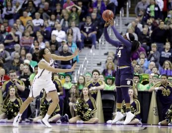 Notre Dame's Arike Ogunbowale, right, hits the game-winning shot as Connecticut's Napheesa Collier, left, watches during overtime in the semifinals of the women's NCAA Final Four college basketball tournament, Friday, March 30, 2018, in Columbus, Ohio. Notre Dame won 91-89. (AP Photo/Ron Schwane)