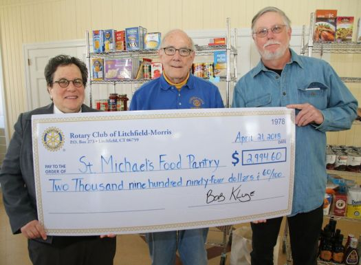 Amy Reichman, director of the food pantry at St. Michael's Church, receives a check from Litchfield-Morris Rotary Club members Chuck Conn, center, and Bob Kluge. John McKenna Republican-American