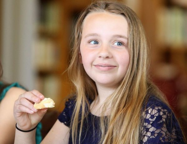 Maggie Rischard, a sixth-grader at James Morris School in Morris, gets set to sample a cookie during the annual sixth-grade tea on Thursday in the Aline Brothier Morris Reading Room. John McKenna Republican-American