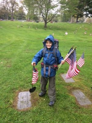 Boy Scout Brian Nelthropp of Troop 3 in Torrington places American flags on the graves of veterans in Hillside Cemetery on May 12. Contributed