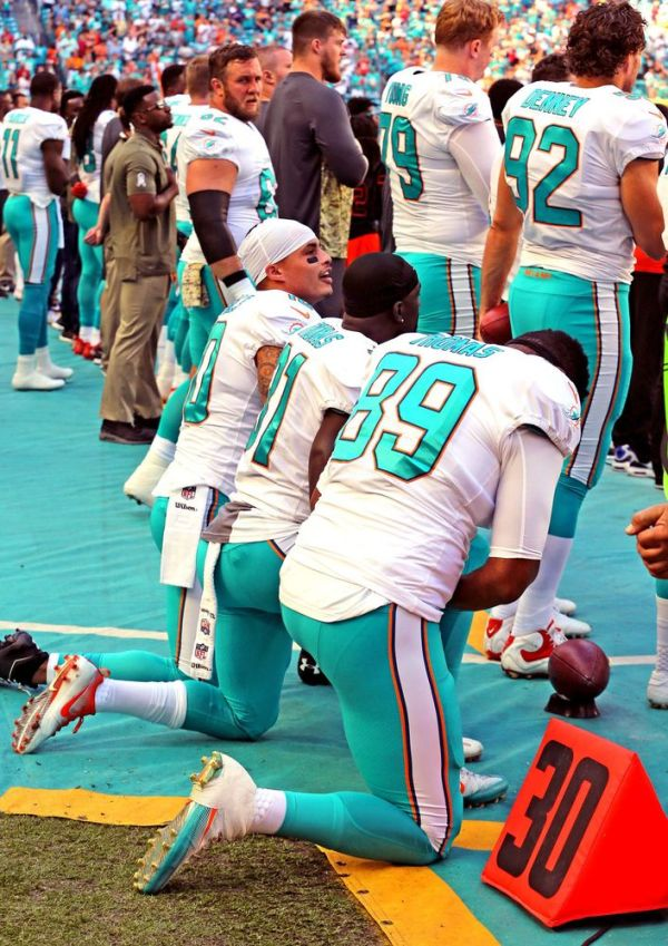 Miami Dolphins Kenny Stills (10), Michael Thomas (31), and Julius Thomas kneel during the national anthem as they prepare to play the Tampa Bay Buccaneers on Sunday, Nov. 19, 2017 at Hard Rock Stadium in Miami Gardens, Fla. (Charles Trainor Jr./Miami Herald/TNS)