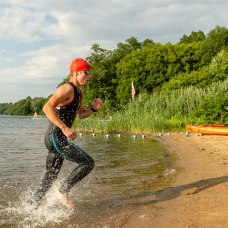 Owen Rowlands of NY is the first to exit the water after a half mile swim in Lake Quassapaug during the the 32nd annual Pat Griskus Sprint Triatalon at Quassy Amusement Park in Middlebury, CT on Wednesday evening. Bill Shettle Republican-American