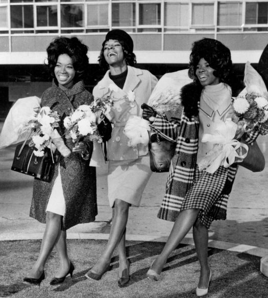In this Nov. 3, 1964, photo, American pop trio Martha Reeves and the Vandellas dance for photographers at an airport in London, arriving for TV appearances and recording work in the British capital. From left are Betty Kelly, Martha Reeves, and Rosalind Ashford. (AP Photo)