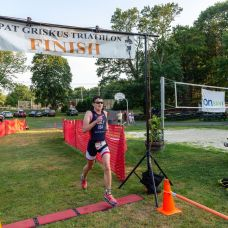 Patrick Daly of Pearl River, NY, the overall winner of the Pat Griskus Triathlon crosses the finish line in under one hour during the the 32nd annual Pat Griskus Sprint Triathalon at Quassy Amusement Park in Middlebury, CT on Wednesday evening. Bill Shettle Republican-American