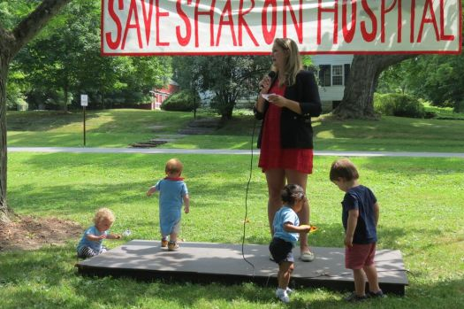 Ruth Epstein Republican-American Lara Hanson Barrett of Kent, surrounded by several toddlers, speaks during Saturday's rally to save Sharon Hospital's maternity unit on the Sharon town Green.